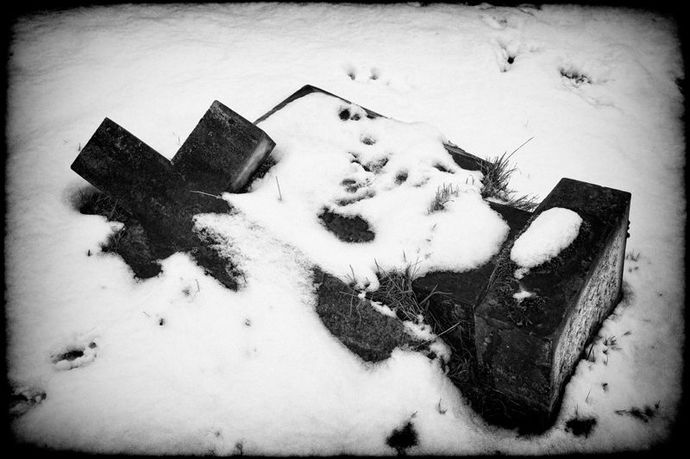 fallen gravestone cross in snow