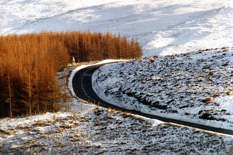 Winding Welsh road with snow and conifers