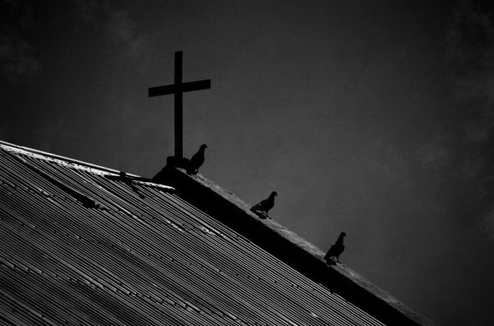 three silhouetted pigeons on church roof next to a cross
