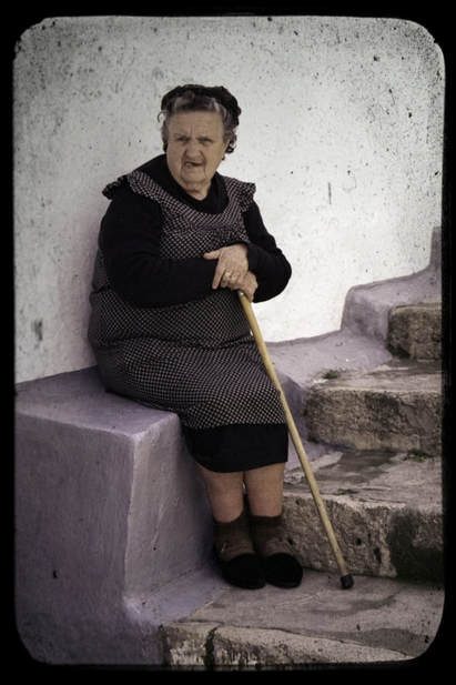 Elderly lady with walking stick sitting on a step